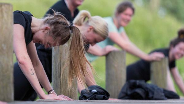 Kvinder, som laver armbøjninger til udendørs træning i søndermarken