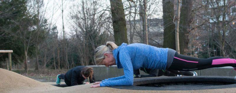 Kvinder, der udfører planke-øvelsen under udendørs træning, i søndermarken