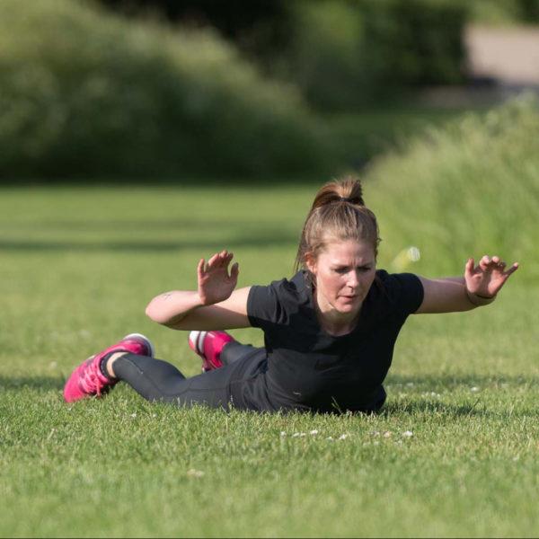 Kvinde, som laver rygøvelser til udendørs træning i søndermarken